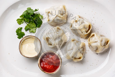 Traditional steamed dumplings Manti with Yogurt and Tomato sauce