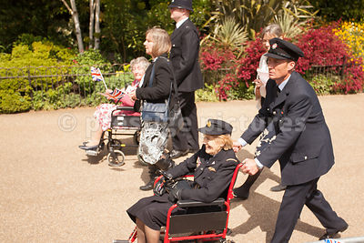 Female RAF Veteran pushed in her wheelchair by Member of the London Fire Brigade