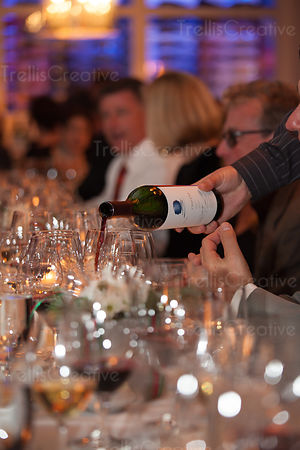Red wine being poured in a winetasting event with a lot of glasses on a table