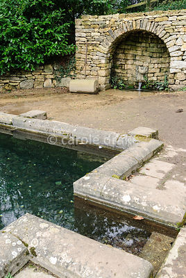 A spring feeds the Plunge Pool emerging from a decorative spout set into a stone arch. Painswick Rococo Garden, Painswick, Glos, UK