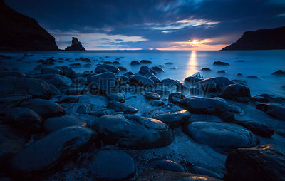 A long exposure of the dark sands and boulders of Talisker Bay as the sun sets. North West Highlands of Scotland.