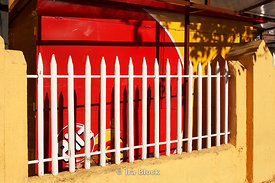 A white fence in front of a red wall in Santiago, Chile.