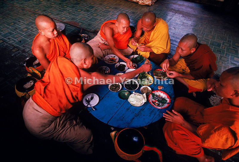 Young monks share a communal breakfast at Wat Xieng Thong, after their daily ritual of binthabat, or rice collecting, throughout town. Every Lao male voluntarily trains as a monk for a least three months of his life.
