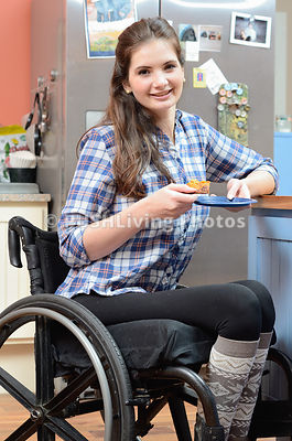 Young woman using a wheelchair relaxing with a slice of cake