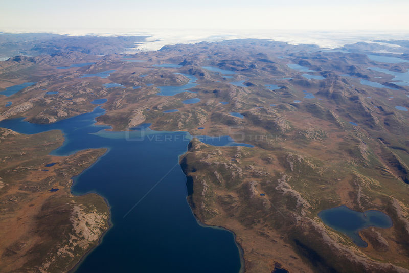 Aerial view of the landscape of the south-west coast of Greenlandbetween Kangerlussuaq and Ilulissat, with glaciers stretching out of the ice shield towards the sea.