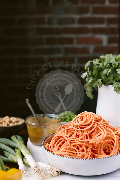 A big bowl of spiralized sweet potato noodles are photographed from the front view along with pad thai sauce, scallions, peanuts, and cilantro.