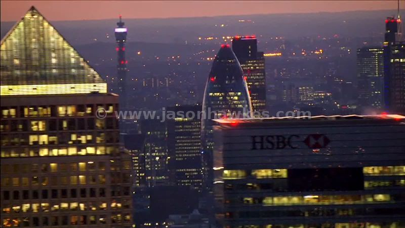 Aerial footage of Canary Wharf and the City of London at night, London, England, UK