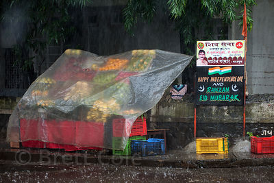 Colorful plastic crates at a vegetable stall are covered in plastic during monsoon rains, Bandra West, Mumbai, India.