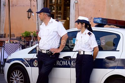One Female and One Male Police Officer Leaning against their Car in Rome