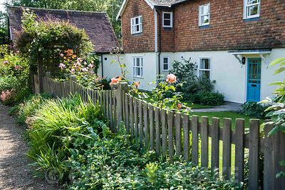 Front garden with pretty picket fence and rose festooned entrance arch over the gate. Church View, Horsmonden, Kent, UK