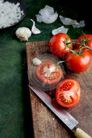 Tomatoes being prepped for a ranchero sauce. Photographed on a green background.