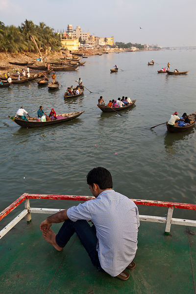 Bangladesh - Dhaka - A man looking over the water taxis from aboard a ferry,  Sadarghat