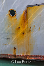 Porthole, Rust, and Sunlit Waves Reflected on a Fishing Boat Hull