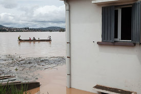 Residents are evacuated on pirogues after the Sisaony river burst and flooded the village of Soavina, a suburb of Antananarivo, after breaking a dam following a night of torrential rain, on February 27, 2015. At least 14 people died in flooding on February 27 in the Madagascan capital Antananarivo after a night of torrential rain caused dams to burst, rescue services said. About 24,000 people were driven from their homes in the floods and several neighbourhoods in the Indian Ocean island nation were being evacuated, the country's emergency management bureau said.