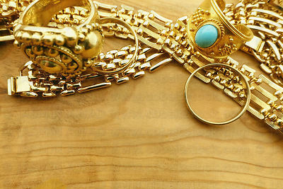 Gold jewelry with copy space on wood background
