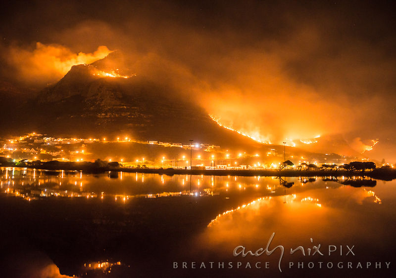 Bright orange flames cover the mountain, reflected in the still water of the vlei at night