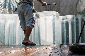 Men moving blocks of ice in Bangkok, Thailand.