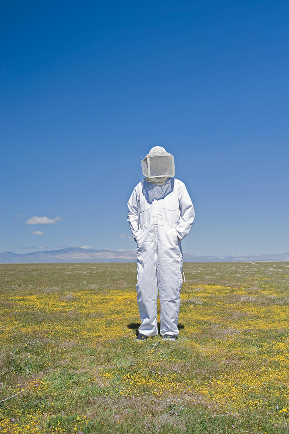bee keeper stands in field
