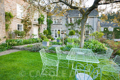 Wirework table and chairs on grass beside the terrace with cherry tree spreading overhead. Brilley Court Farm, Whitney-on-Wye, Herefordshire, UK