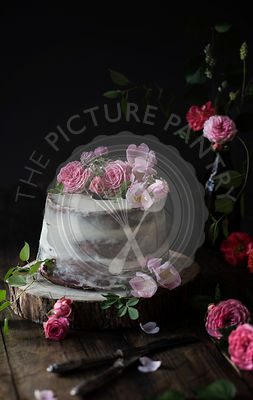 Naked cake decorated with roses on wooden table