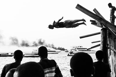A man jumps into the sea in front of a burning boat during Zanzibar's Sauti za Busara festival, 2012.