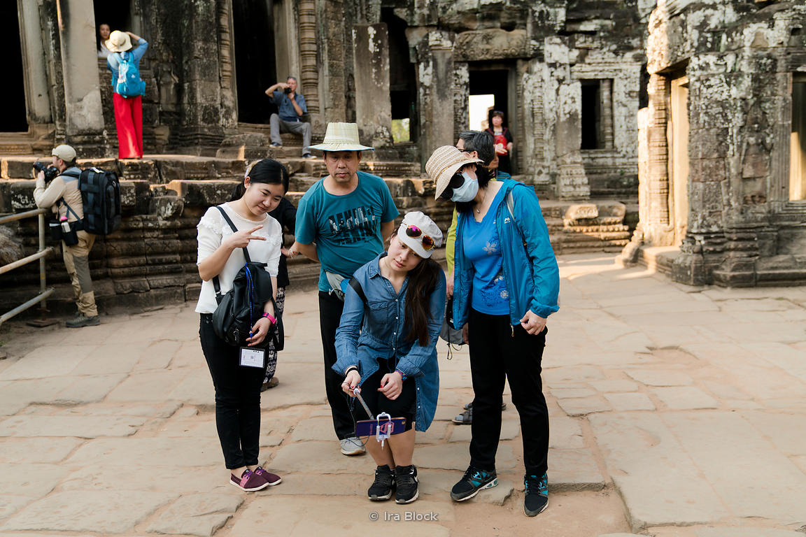 Tourists pose for pictures at Bayon Temple in Siem Reap, Cambodia.