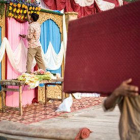 Workers prepare the stage for a wedding and a florist creates a floral decoration on a canopy above which the bride and groom will sit