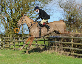 Adam Cooke jumping a hedge above Wilson's Covert