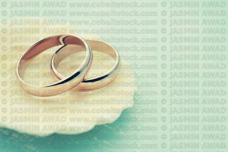 Rose gold wedding rings on seashell with light blue wood background Digital color processing