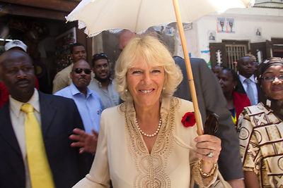 Duchess of Cornwall shelters herself from the sun in 32 C during an official royal visit to Zanzibar with the Prince of Wales, 8 November 2011.