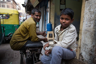 A boy and his father at their shop, Paharganj, Delhi, India