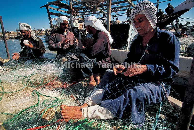 Persian Gulf fishermen mend their nets in Basra. Even though over half of the world's oil reserves are here, fishing has remained a major part of the economy for centuries.