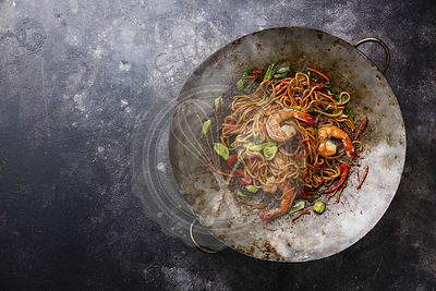 Udon noodles stir-fried with Tiger shrimps and vegetable in wok cooking pan on dark background copy space