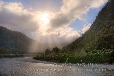 Sunbeams shining down through clouds onto a river winding between forested hills