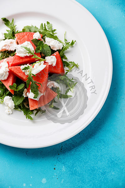 Watermelon salad with arugula, ricotta cheese and mint on blue background close-up