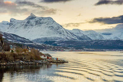 Snow covered Mountains and orange glistening sea with small houses on the waters edge.