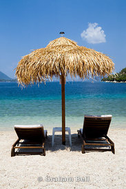 Straw umbrella and sun loungers, Spilia Bay, Spartochori, Meganisi, Lefkada, Ionian Islands, Greece.