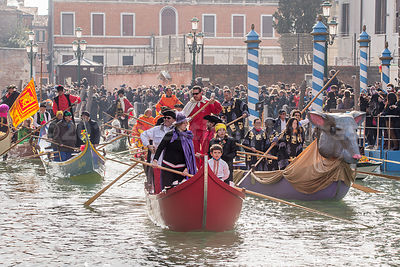 Boat with Rat Figurehead and boatmen wearing colourful Costumes in the Venice Carnival Water Parade on the Rio di Cannaregio Canal