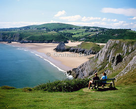 Couple sitting on bench,  Pennard Cliffs overlooking Three Cliffs Bay, Gower Peninsula, South Wales.