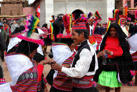 Young man serving alcohol between dances at San Santiago festival , Taquile Island , Peru