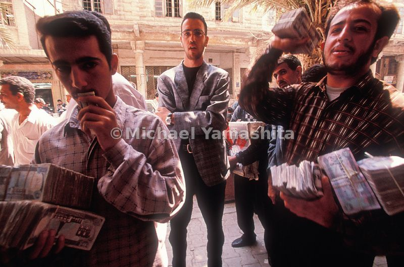 Weighed down with dinars, money changers stalk a Baghdad street where foreign journalists, merchants, and United Nations officials pas by with their hard currencies.
