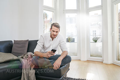 Man sitting on couch looking at cell phone