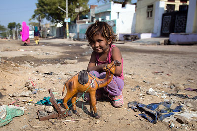 A girl plays with a toy camel, Pushkar, Rajasthan, India. A favorite photo, this was completely unstaged, she even chose to stop playing and chose how she wanted to hold herself. This is typical of my India photos.