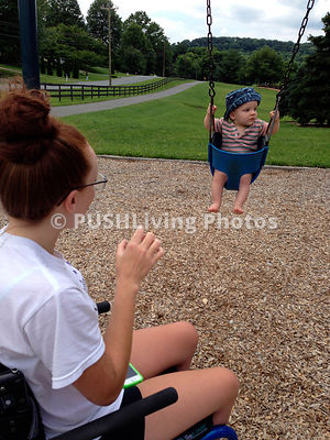 Woman in a wheelchair pushing a young child in a swing