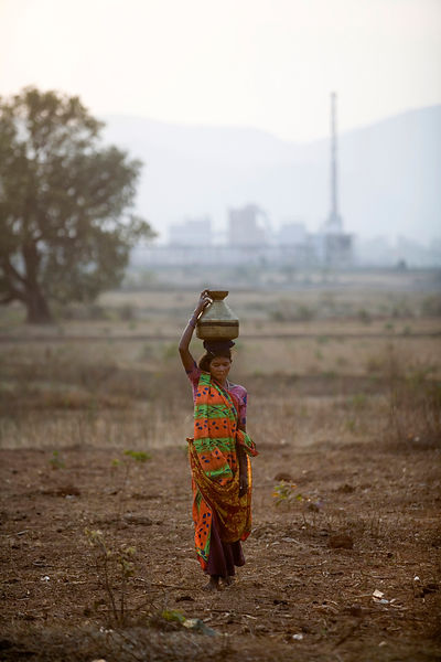 A woman carries a pot of water