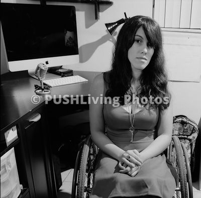 Young woman in a wheelchair at her computer in her room