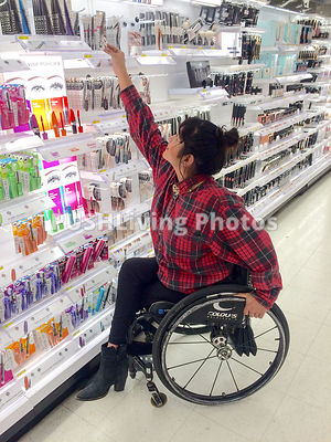 Young woman using a wheelchair shopping for beauty products