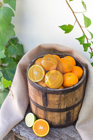 bucket of oranges, with sackcloth, on an old wooden bench against ivy covered white wall