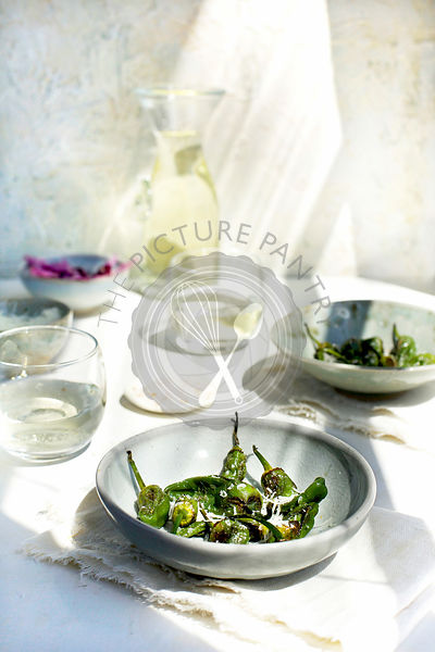 Roasted Padron Peppers with Mandarin Maldon Salt served with white wine.  Photographed on a white plaster background.