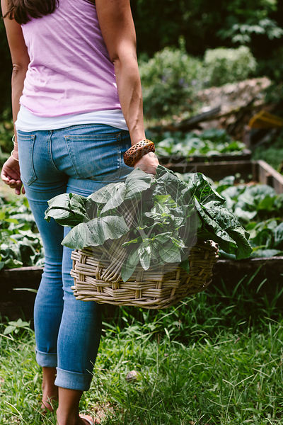 A woman is photographed from behind while she is holding a basket full of freshly picked greens in her hand in a farmer's market.